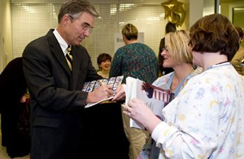 Hospital CEO Bruce Crowther signing books for NCH nurses; author O'Connor signing books in background