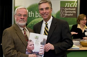 Area resident John Welzenbach (left) with CEO Bruce Crowther. At age 8, John was a poster boy for NCH's initial fund-raising efforts. He's the boy on the book cover.